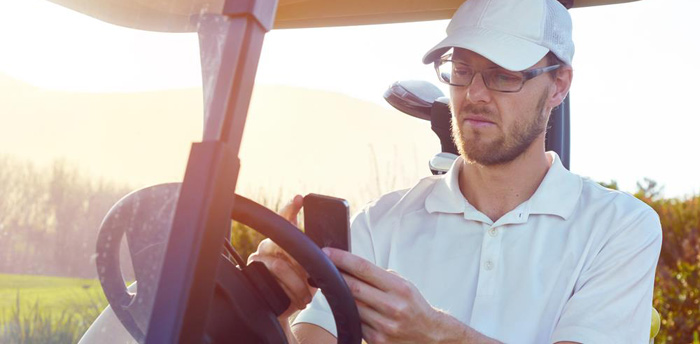 man sitting in golf cart using his fancy golf GPS